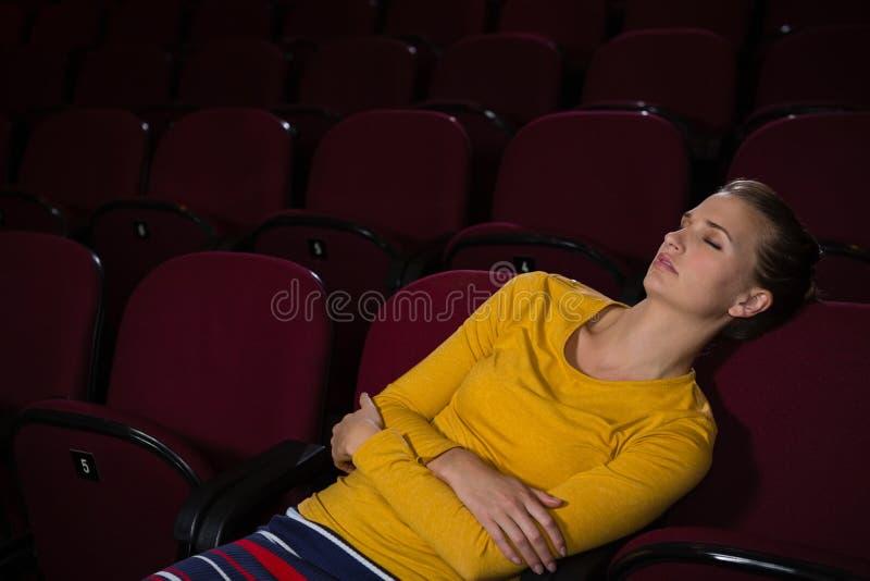 Mulher que dorme em um teatro de filme fotografia de stock