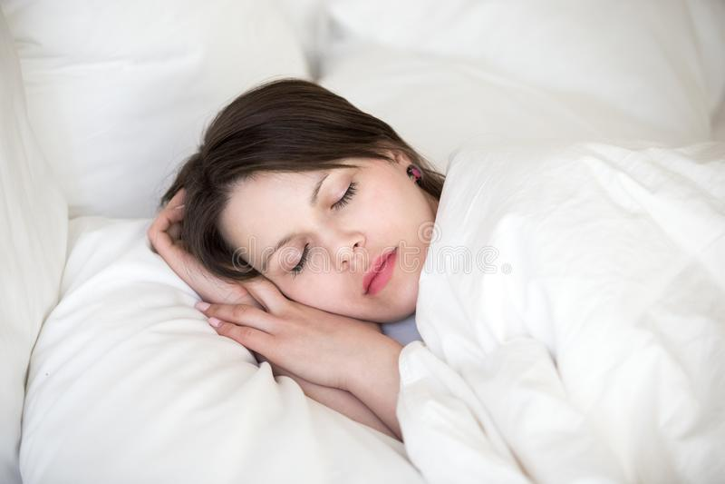 Mulher que dorme na cama na coberta ortopédica do descanso com edredão foto de stock royalty free
