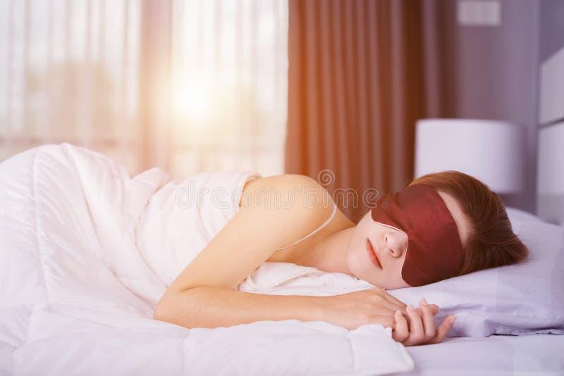 Mulher que dorme na cama com máscara de olho no quarto com luz suave imagens de stock