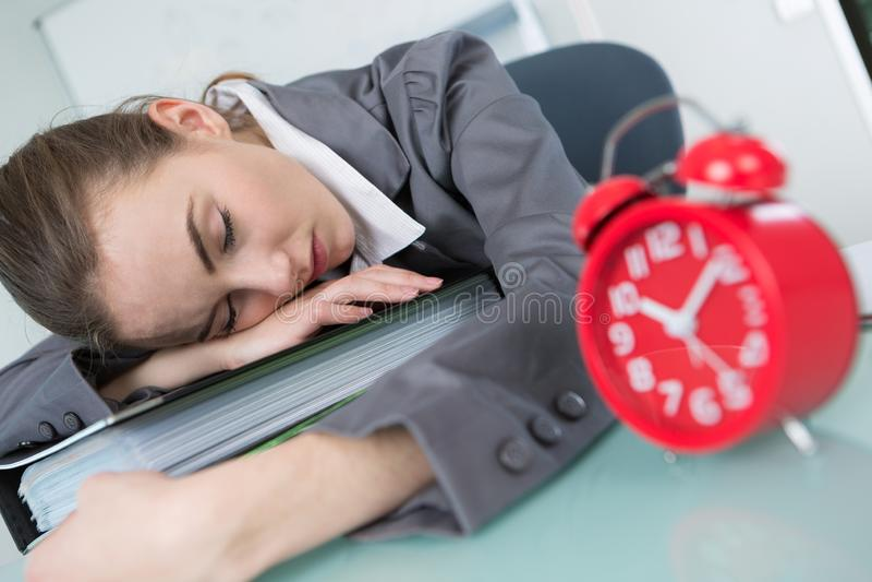 Mulher que dorme na tabela ao trabalhar imagem de stock
