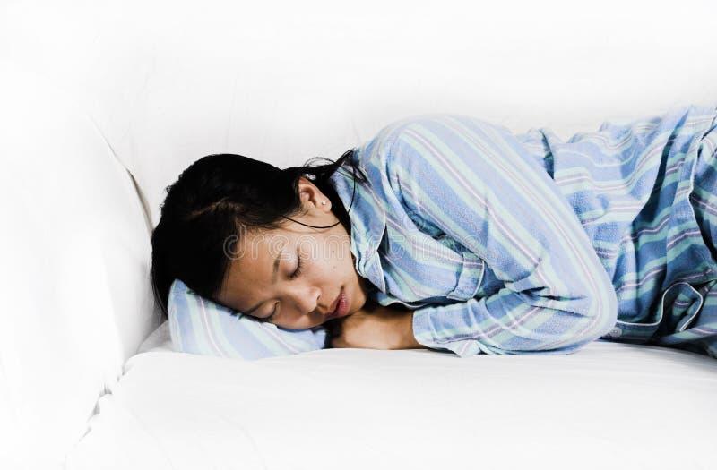 Mulher que dorme no sofá imagem de stock