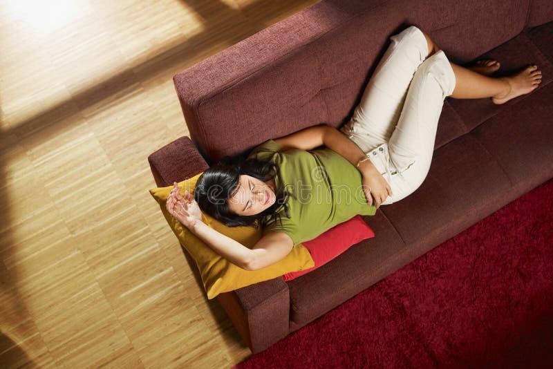 Mulher que dorme no sofá imagens de stock royalty free