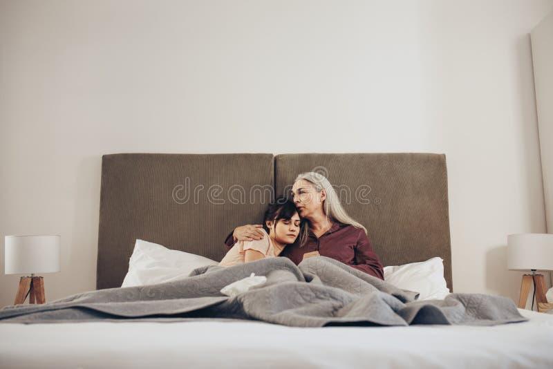 Mulher que dorme nos braços de sua mãe na cama imagens de stock
