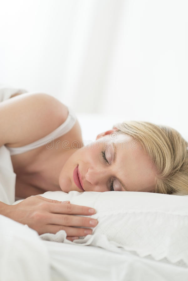 Mulher que dorme pacificamente na cama foto de stock royalty free