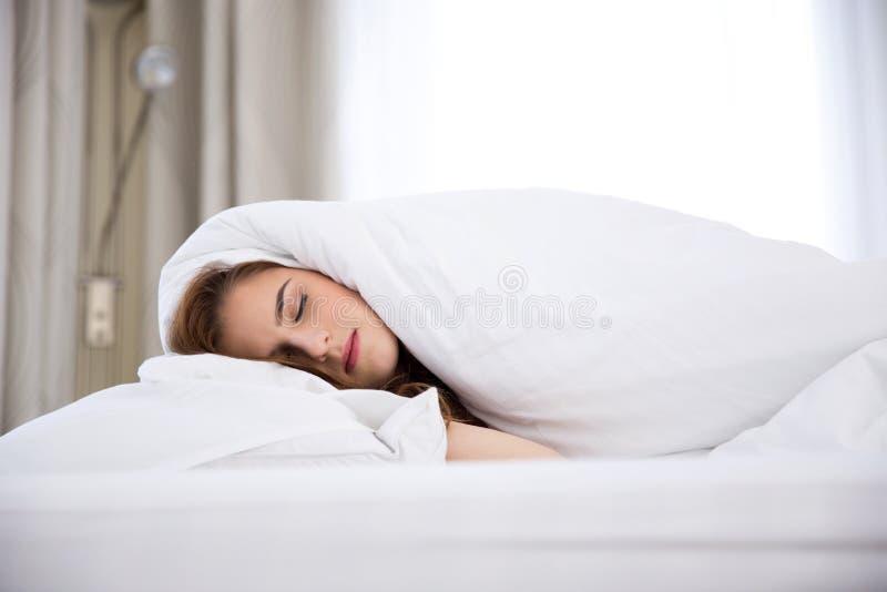 Mulher que dorme sob uma cobertura imagens de stock royalty free
