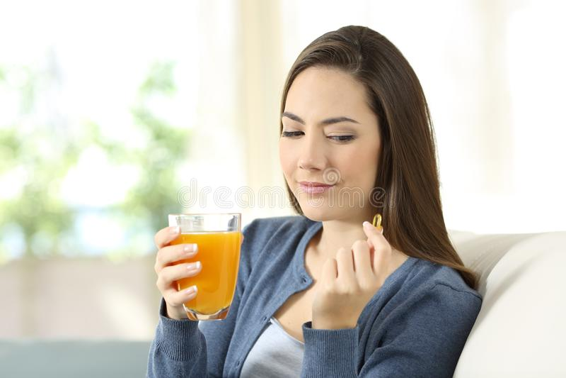 Mulher que duvida entre o comprimido da vitamina ou o suco de laranja imagens de stock