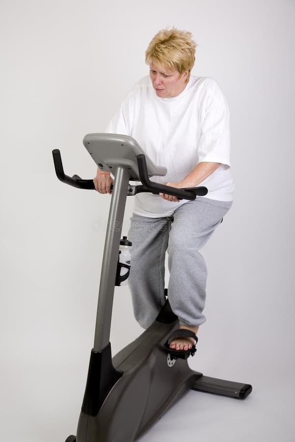 Mulher que elabora na bicicleta fotografia de stock royalty free