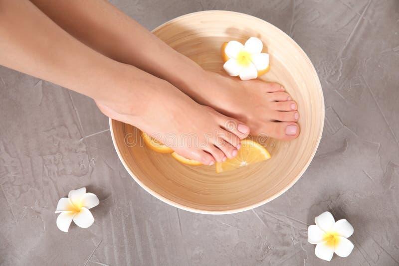 Mulher que embebe seus pés na bacia com água, as fatias alaranjadas e a flor no fundo cinzento, vista superior foto de stock royalty free
