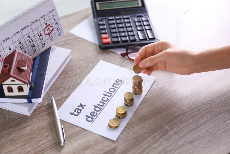 Mulher que empilha moedas no papel com palavras DEDUÇÕES FISCAIS na tabela foto de stock