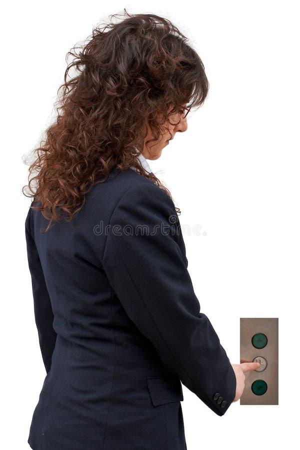 Mulher que empurra a tecla do elevador foto de stock
