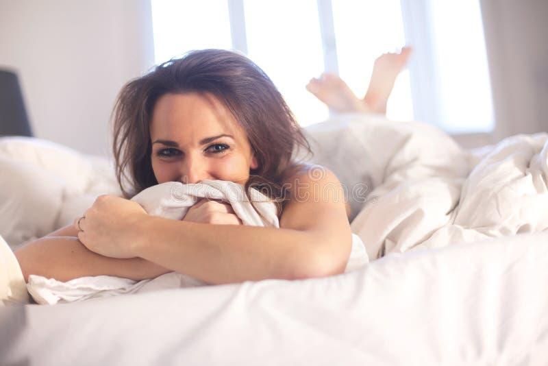 Mulher que encontra-se em sua cama que tem o divertimento imagem de stock