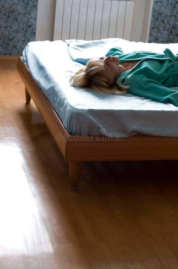 Mulher que encontra-se na cama imagens de stock