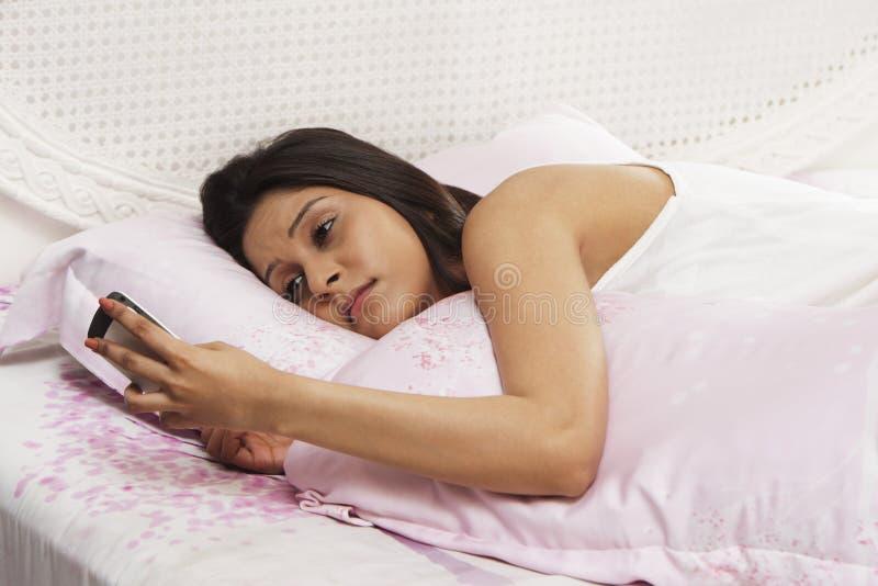 Mulher que encontra-se na cama e que guarda um telefone celular imagens de stock