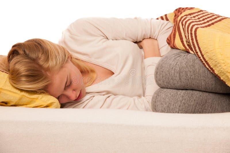 Mulher que encontra-se na cama que guarda a barriga devido à dor no stomac fotos de stock