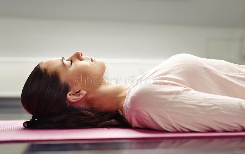 Mulher que encontra-se na esteira da ioga que relaxa seus músculos imagens de stock royalty free
