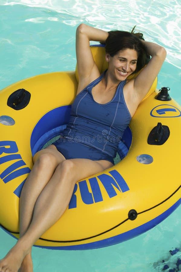 Mulher que encontra-se na jangada inflável na opinião elevado da piscina. fotografia de stock royalty free
