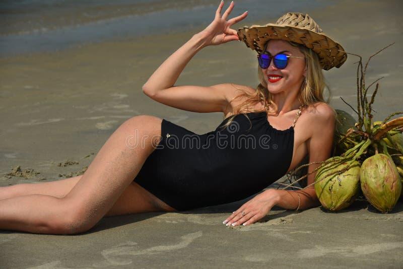Mulher que encontra-se na praia tropical que veste o roupa de banho preto e o chapéu que apreciam suas férias fotografia de stock