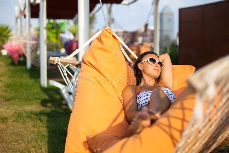 Mulher que encontra-se na rede Dia ensolarado quente Mulher que relaxa no hammock Close-up de uma mulher feliz nova que encontra- fotografia de stock