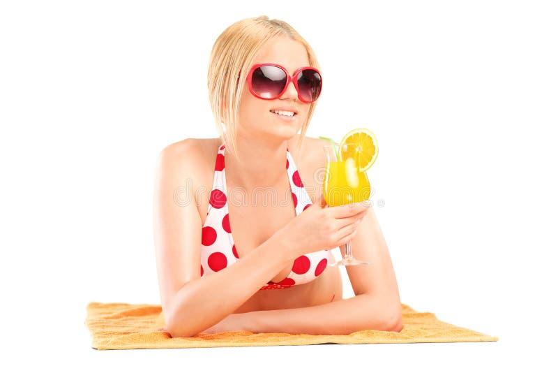 Mulher que encontra-se na toalha e que guarda um cocktail foto de stock