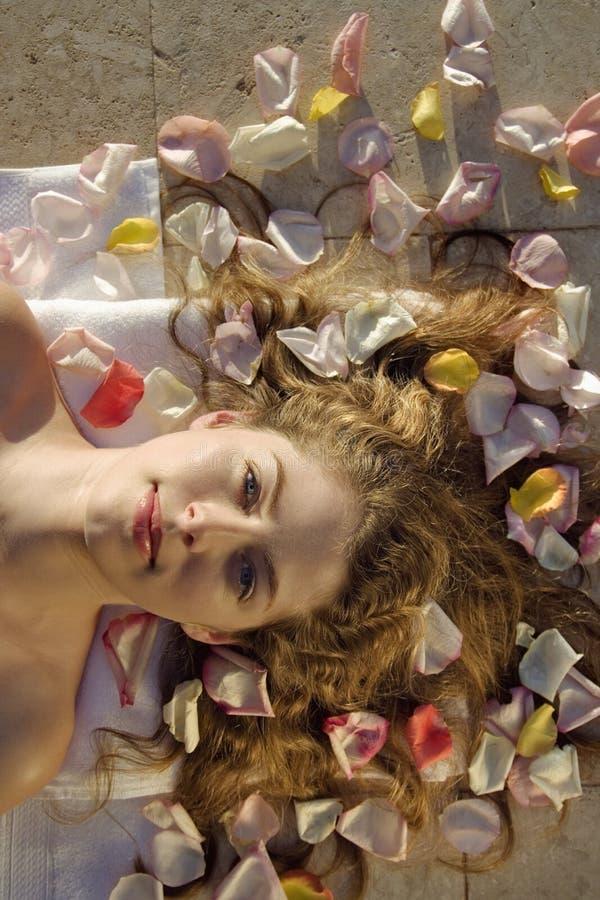 Mulher que encontra-se nas pétalas cor-de-rosa. imagens de stock