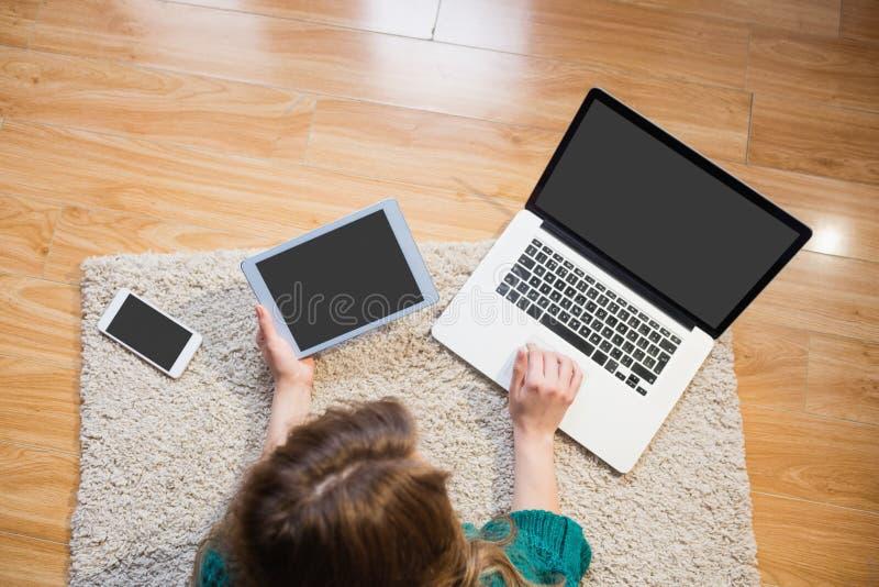 Mulher que encontra-se no assoalho ao usar seus portátil e tabuleta fotos de stock