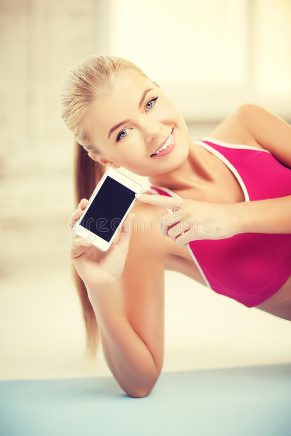 Mulher que encontra-se no assoalho com smartphone fotos de stock