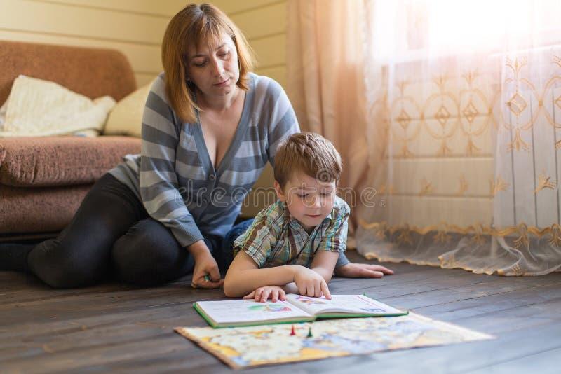 A mulher que encontra-se no assoalho contratou nas lições com um filho novo fotos de stock