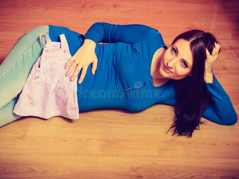 Mulher que encontra-se no assoalho que mostra sua barriga grávida foto de stock royalty free