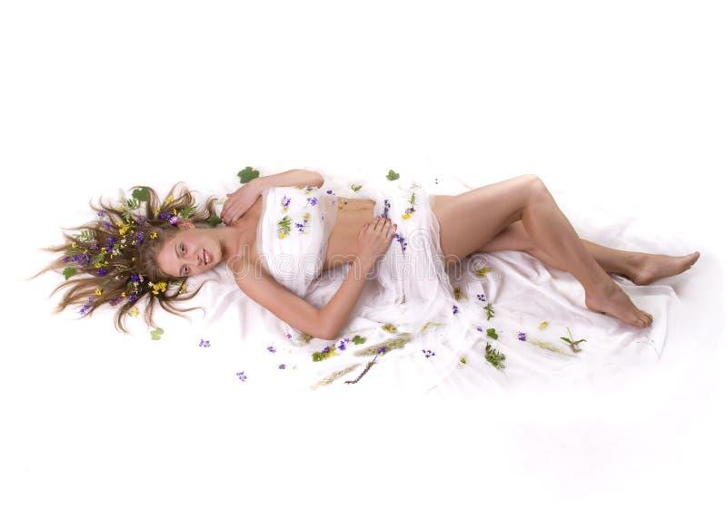 Mulher que encontra-se no flores fotografia de stock