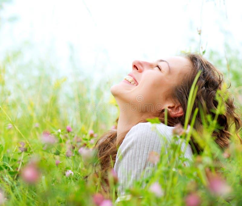 Mulher que encontra-se no prado das flores imagens de stock