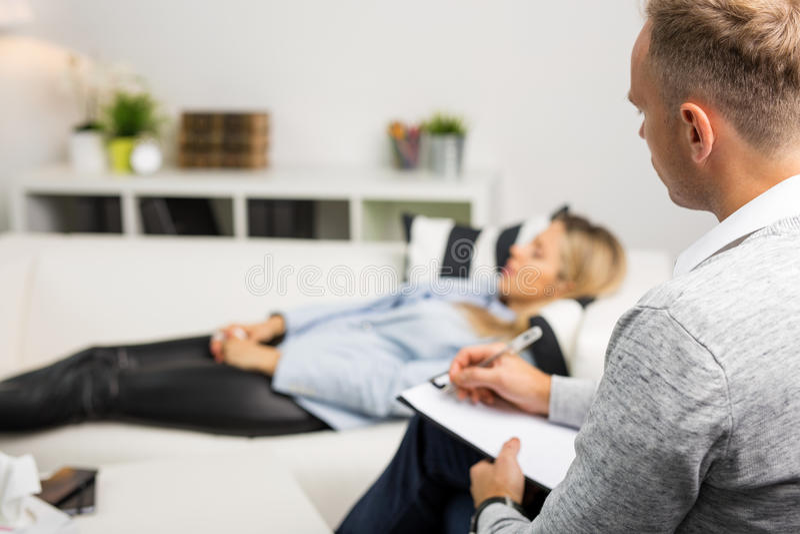 Mulher que encontra-se no sofá no escritório dos doutores fotografia de stock
