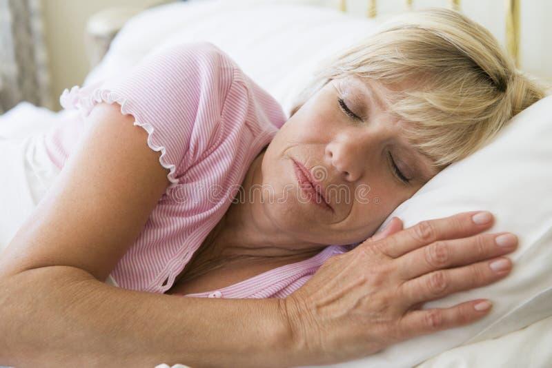 Mulher que encontra-se no sono da cama imagem de stock