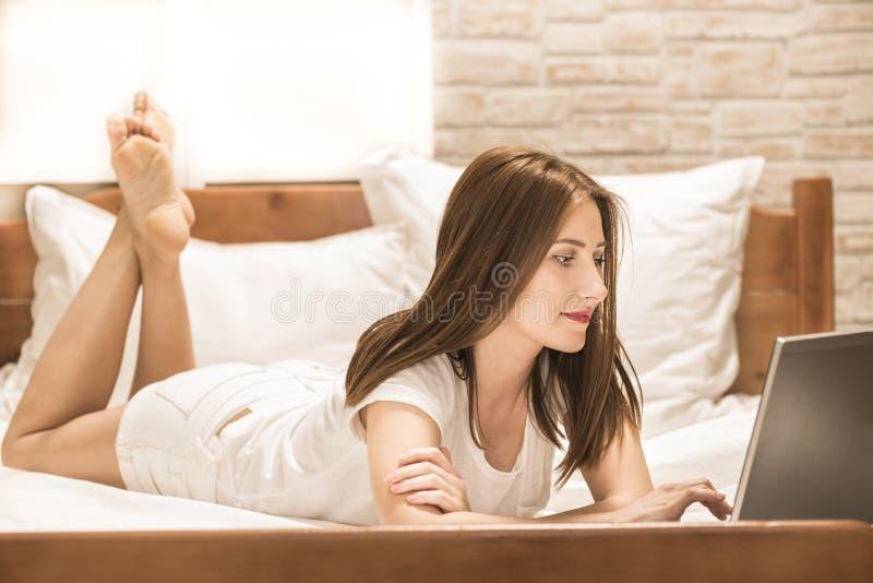 Mulher que encontra-se para baixo a cama na frente de seu portátil fotografia de stock