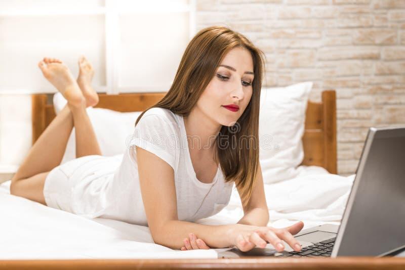 Mulher que encontra-se para baixo a cama na frente de seu portátil imagens de stock royalty free