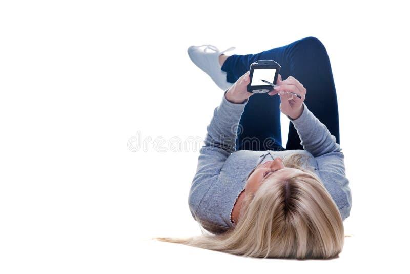 Mulher que encontra-se para baixo escrevendo em seu pda isolado imagem de stock