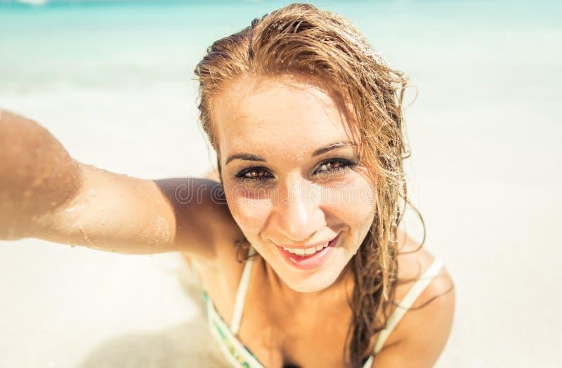 Mulher que encontra-se para baixo na areia branca foto de stock royalty free