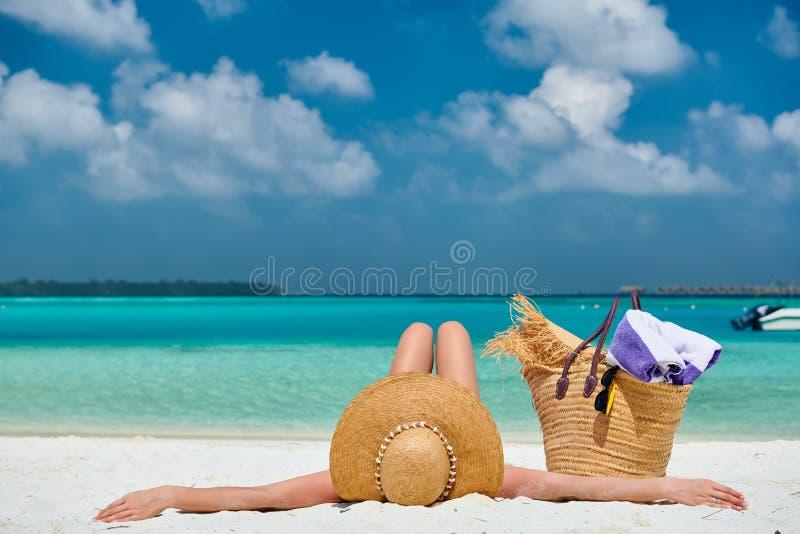 Mulher que encontra-se para baixo na praia imagens de stock