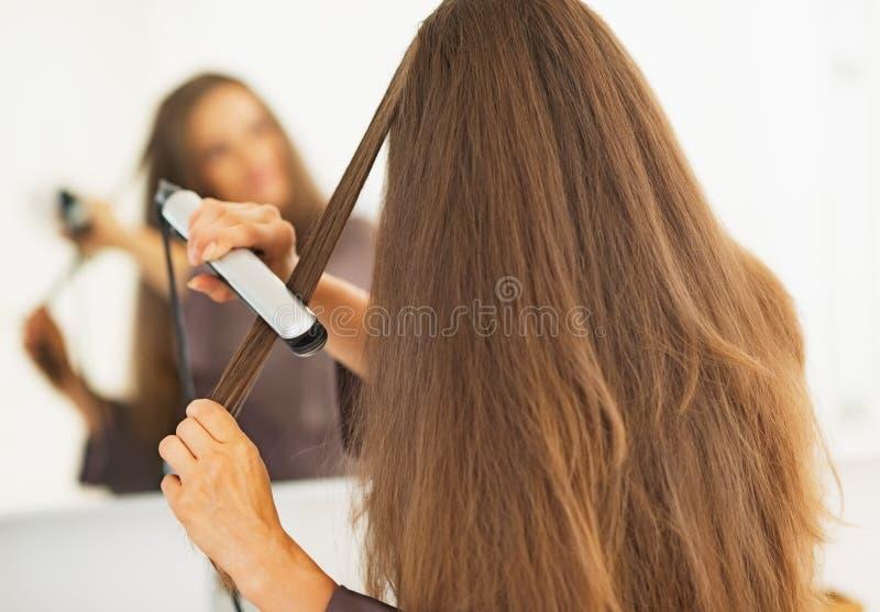 Mulher que endireita o cabelo com straightener imagem de stock royalty free
