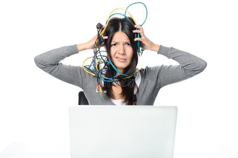 Mulher que enrola cabos sobre a cabeça ao usar o portátil fotografia de stock royalty free