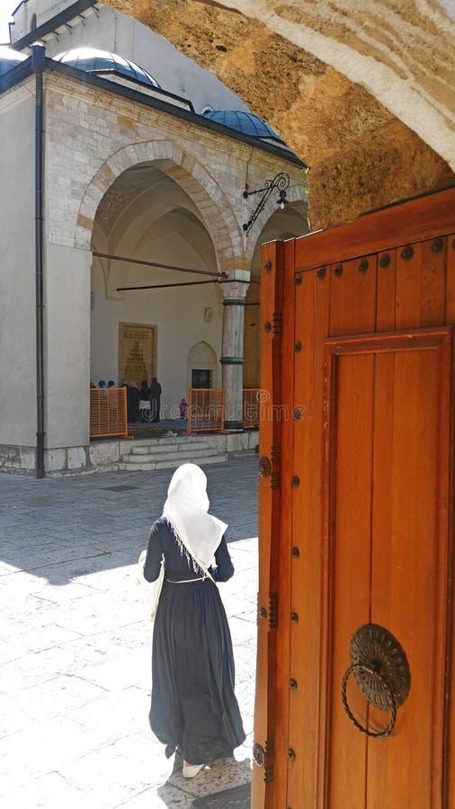 Mulher que entra em uma mesquita em Sarajevo imagens de stock