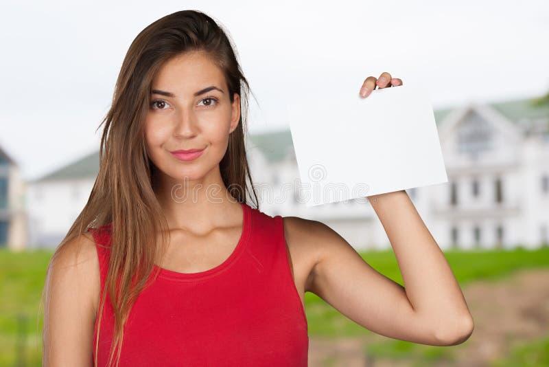 Mulher que entrega um cartão em branco fotografia de stock