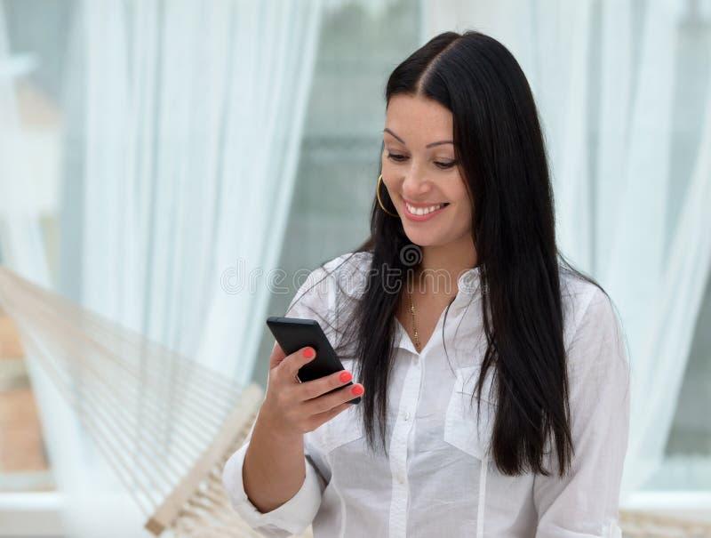 Mulher que envia uma mensagem de texto de seu telefone celular fotografia de stock royalty free