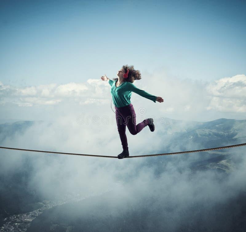 Mulher que equilibra em uma corda acima das nuvens e das montanhas, quando música de escuta fotos de stock