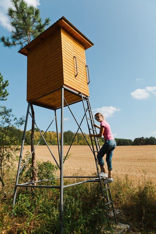 Mulher que escala no assento alto para caçadores foto de stock