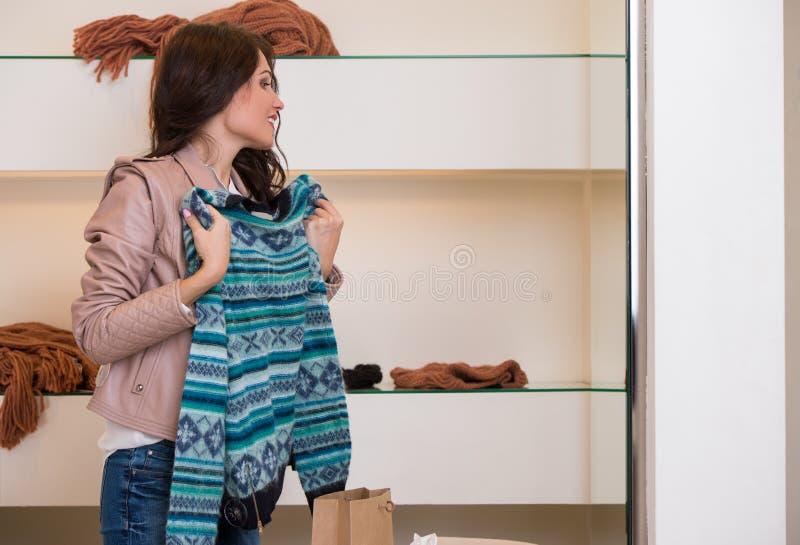 Mulher que escolhe a camiseta na compra imagens de stock