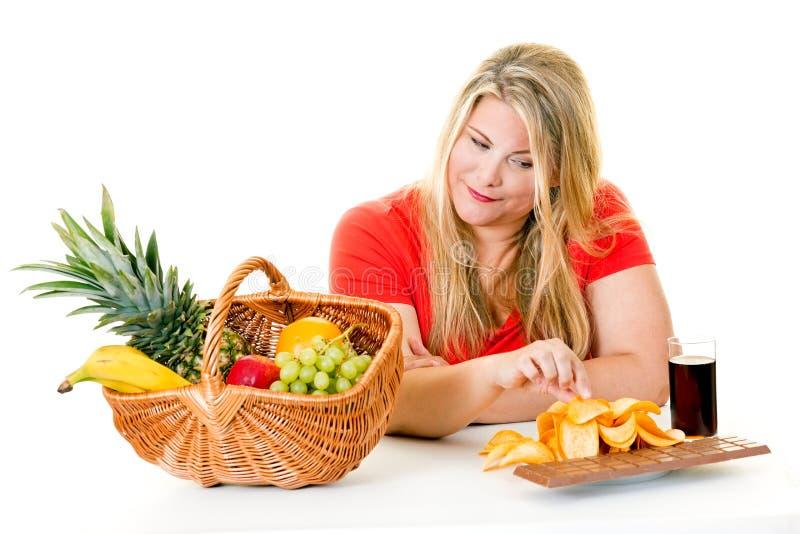 Mulher que escolhe a comida lixo sobre o fruto saudável imagem de stock royalty free