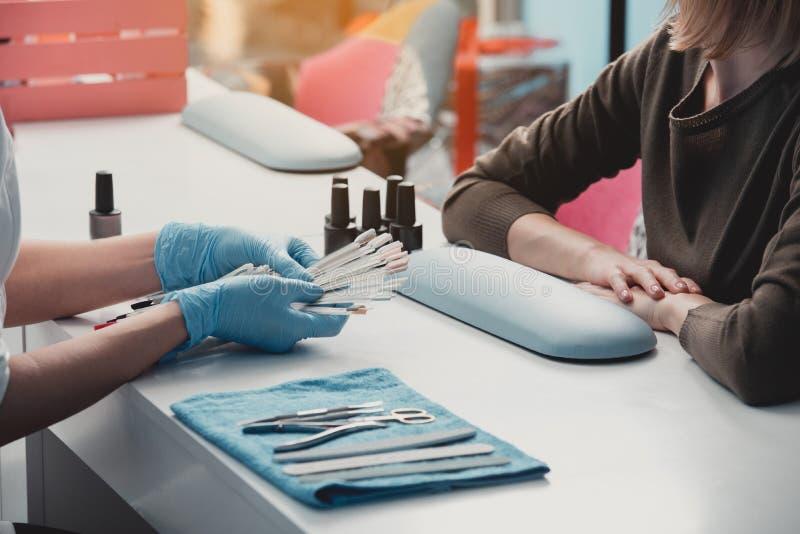 Mulher que escolhe a cor para o tratamento de mãos fotografia de stock