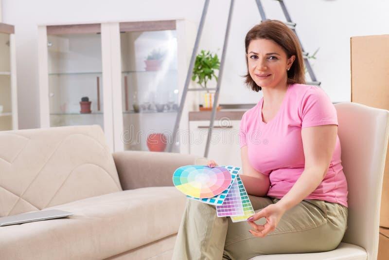 A mulher que escolhe a cor para a renova??o lisa fotografia de stock royalty free