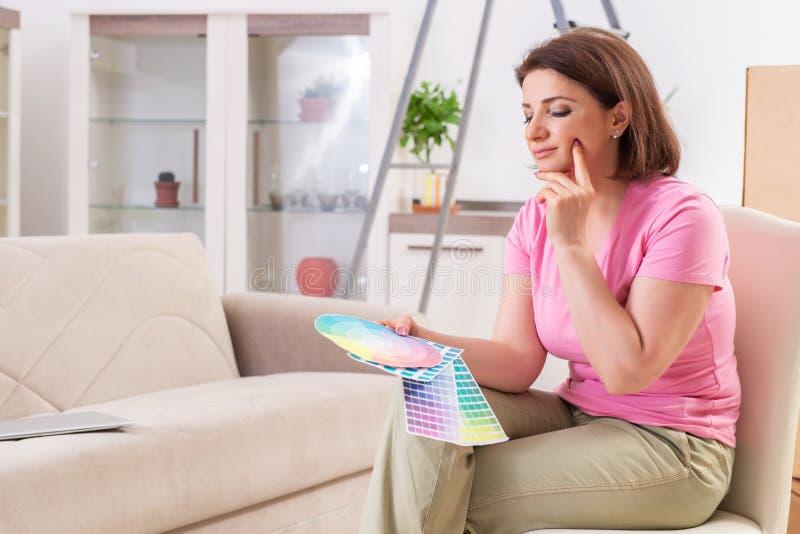 A mulher que escolhe a cor para a renova??o lisa imagem de stock royalty free