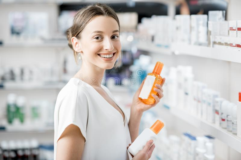 Mulher que escolhe a loção da proteção solar na farmácia fotografia de stock